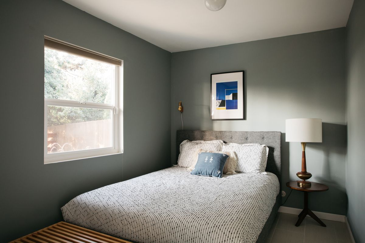 A small bedroom with light gray walls and a window.