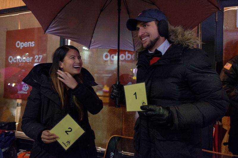 Faye Javier (Left, 33, Coney Island, NY) and her boyfriend Justin Callan (Right (28, Coney Island, NY) hold up their #1 and #2 customer cards, as they wait in line for the opening of Jollibee
