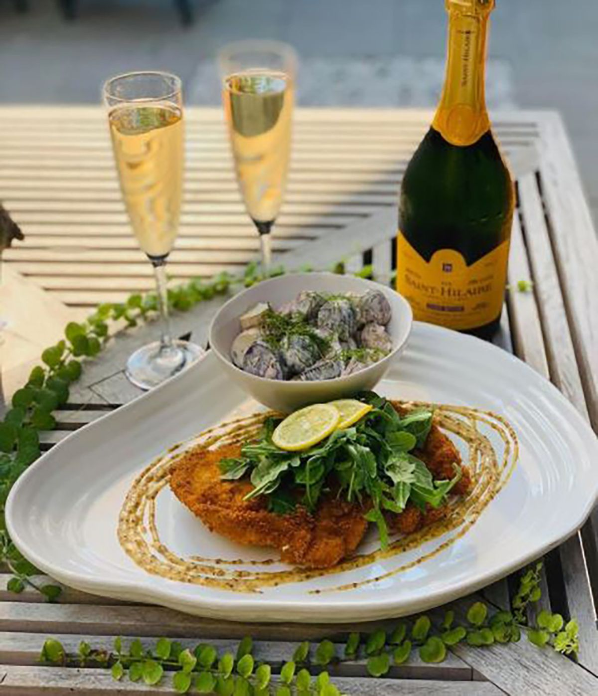 A table setting with champagne and schnitzel