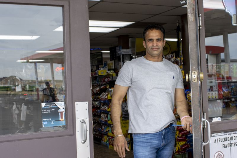 Man wearing a t-shirt opens the door to a store, toward the viewer.