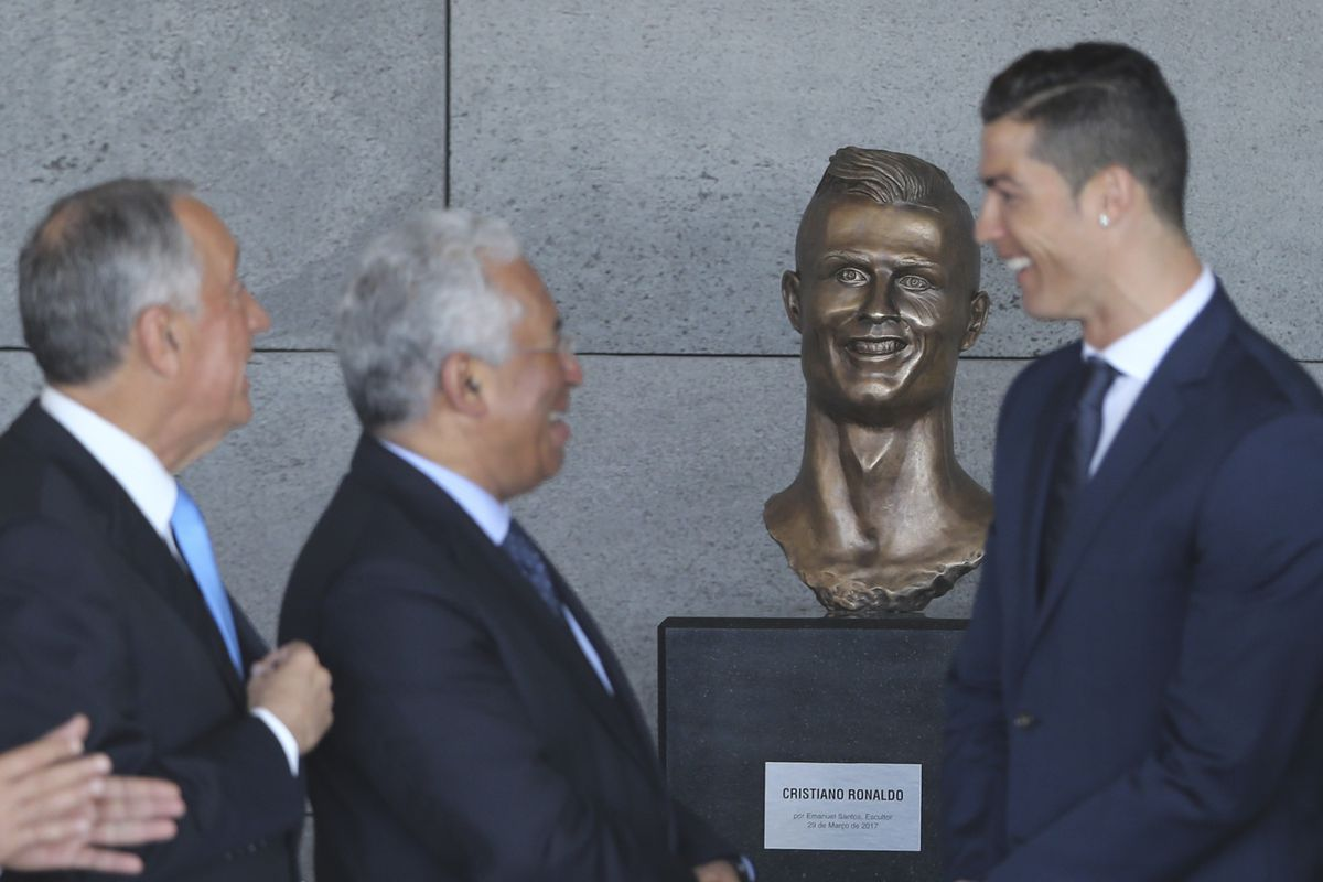 Portuguese president Marcelo Rebelo de Sousa, left, Portuguese Prime Minister Antonio Costa, 2nd left and Real Madrid's Cristiano Ronaldo stand next to a bust of the player.
