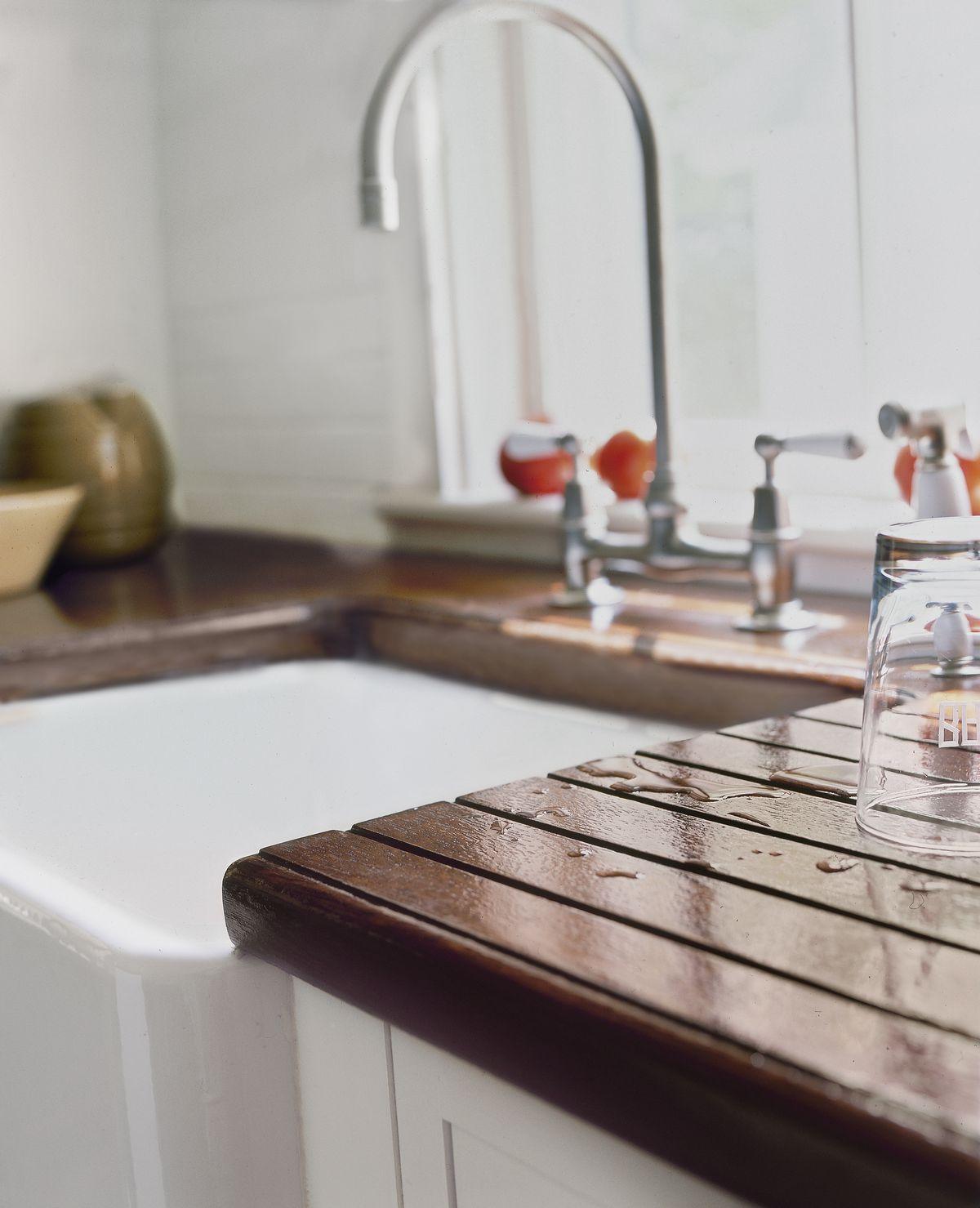 Wet wood countertop by sink.