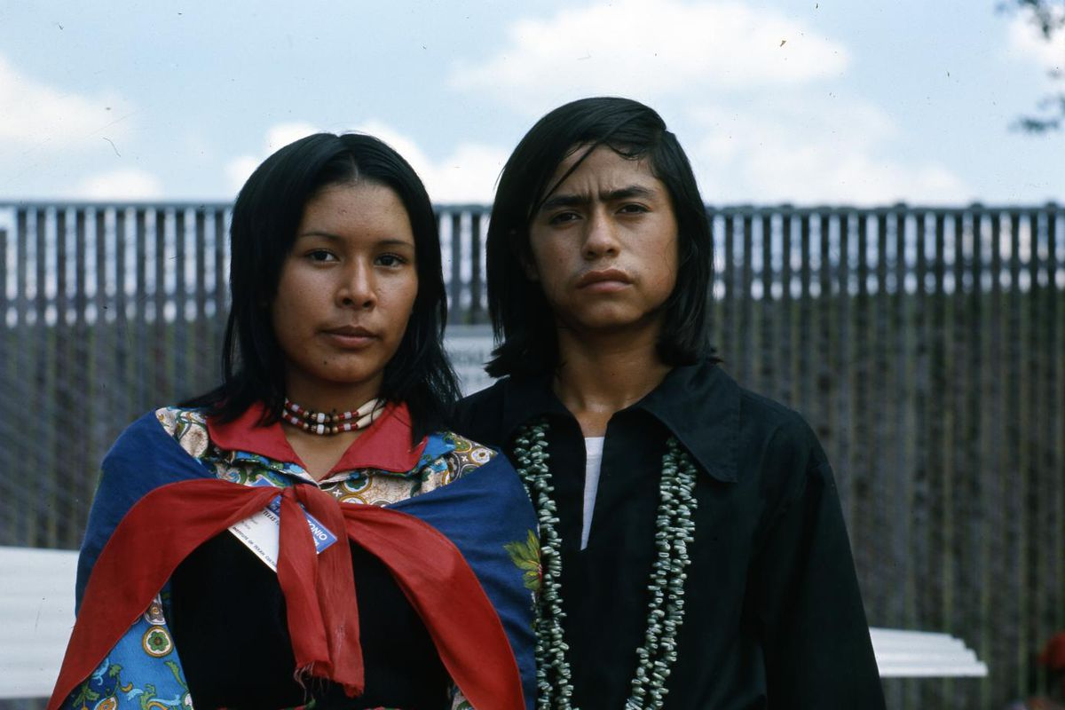 """""""Dressed in traditional garments, the woman is wearing a black dress with colorful sleeves and a colorful shawl drawn over her shoulders. A tight beaded necklace is around her neck and she is holding a large black and white feather. The man is wearing a b"""