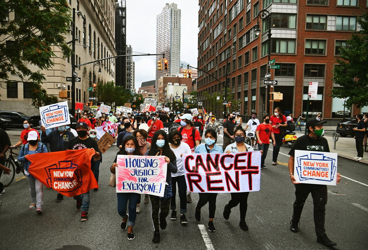 """Protesters marching down a New York street carry signs that read, """"Cancel rent,"""" """"Housing justice for everyone,"""" and """"New York Communities Change."""""""