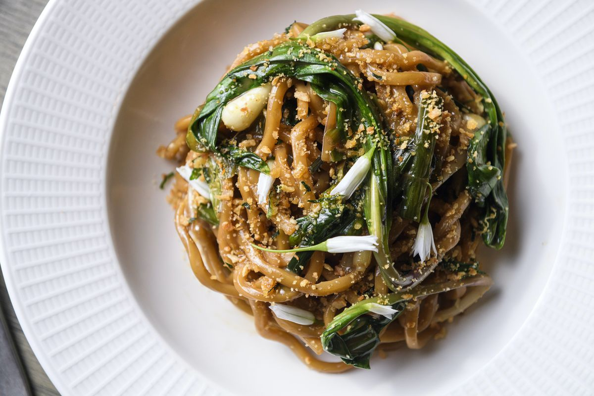 A white plate with bigoli pasta with spring onions.