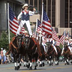 A woman straddles two horses while participating in the Days of '47 Parade in Salt Lake City on Friday.