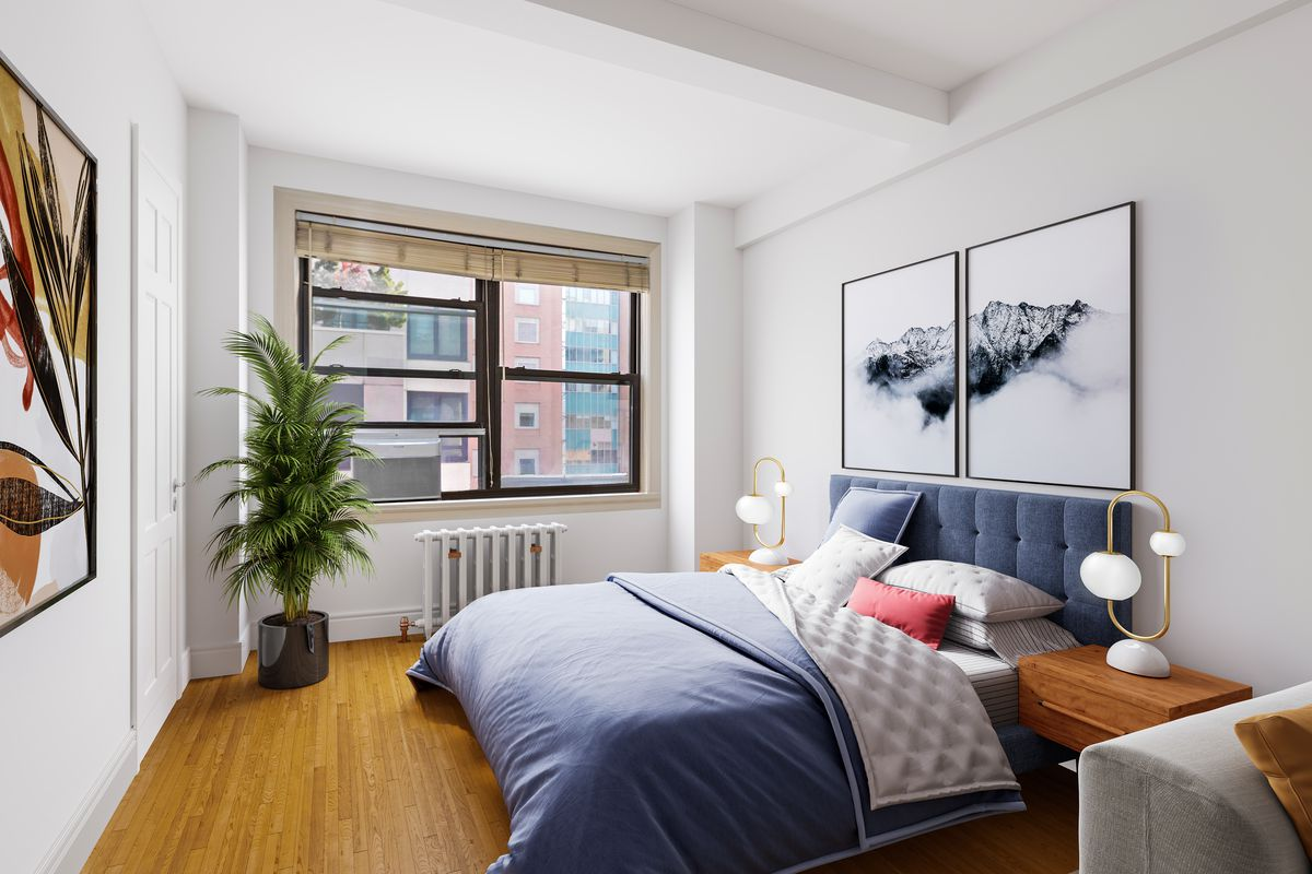 A bedroom with a large bed, a window, beamed ceilings, and hardwood floors.