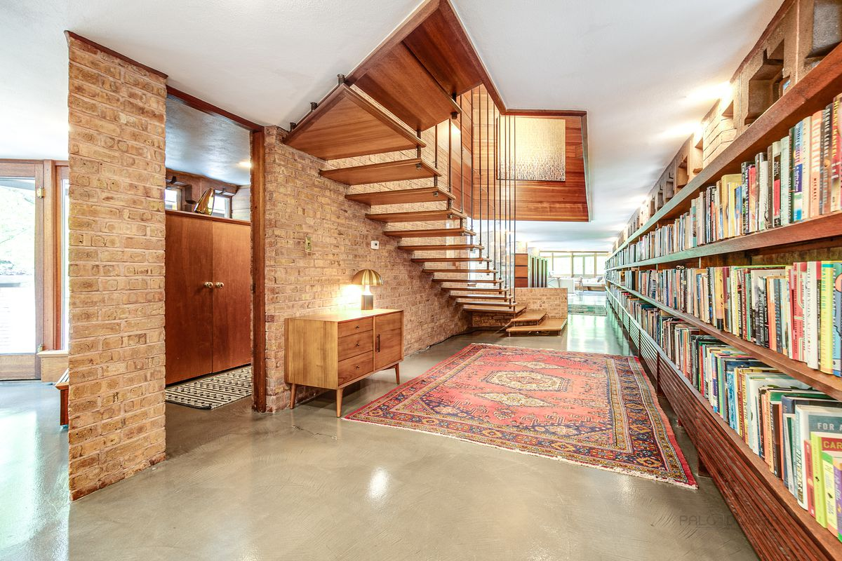 A hallway has a floating staircase on the left and built-in bookshelves on the right.