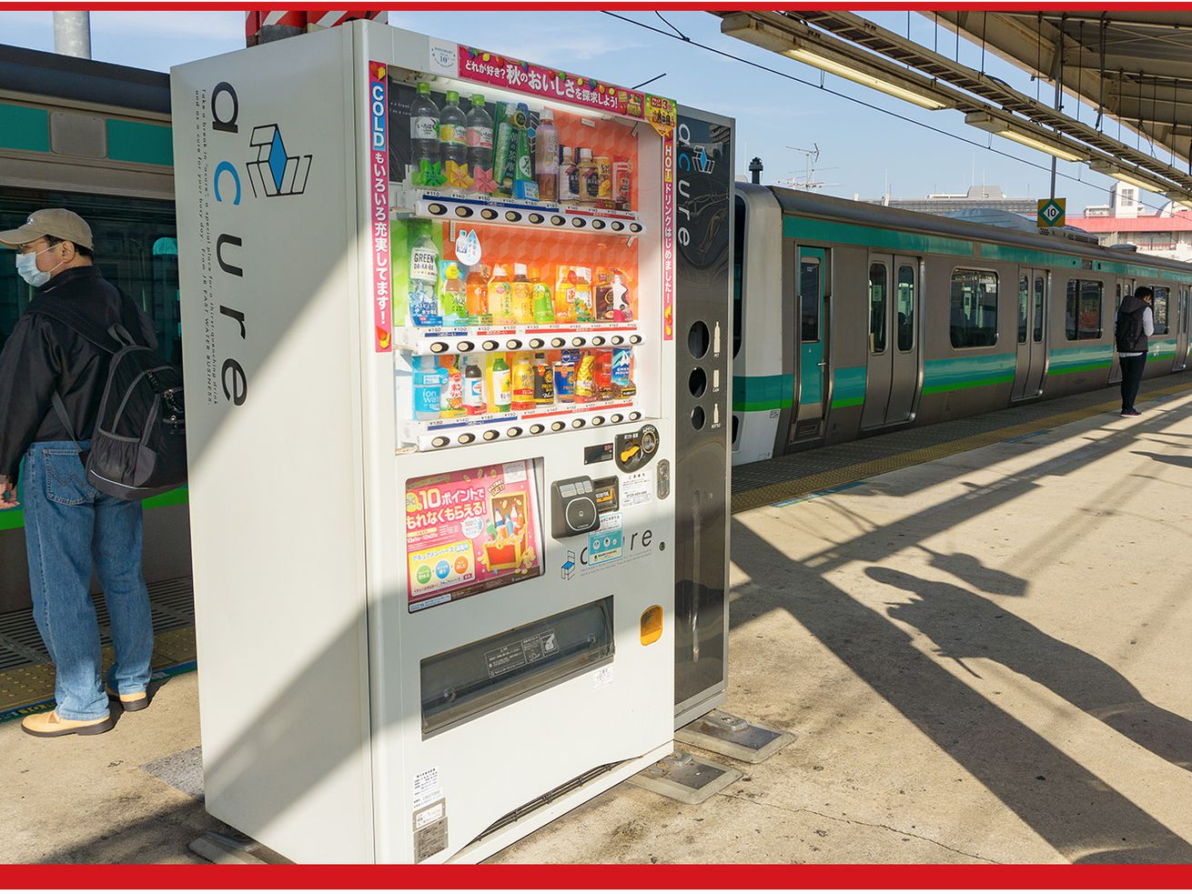Vending machines containing drinks sit on an above ground train platform in Japan.
