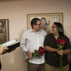 Ariel Ulloa Gonzalez, center, and Gregory Enke are married by State Sen. Jim Dabakis, left, as Enke's daughter, Jessica Hoague, right, looks on at the Salt Lake County Clerk's Office in Salt Lake City, Monday, Oct. 6, 2014.