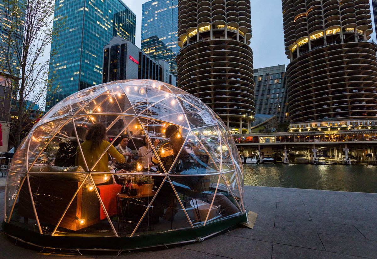 A plastic dome that looks like an igloo for two people to gather near the Chicago River.