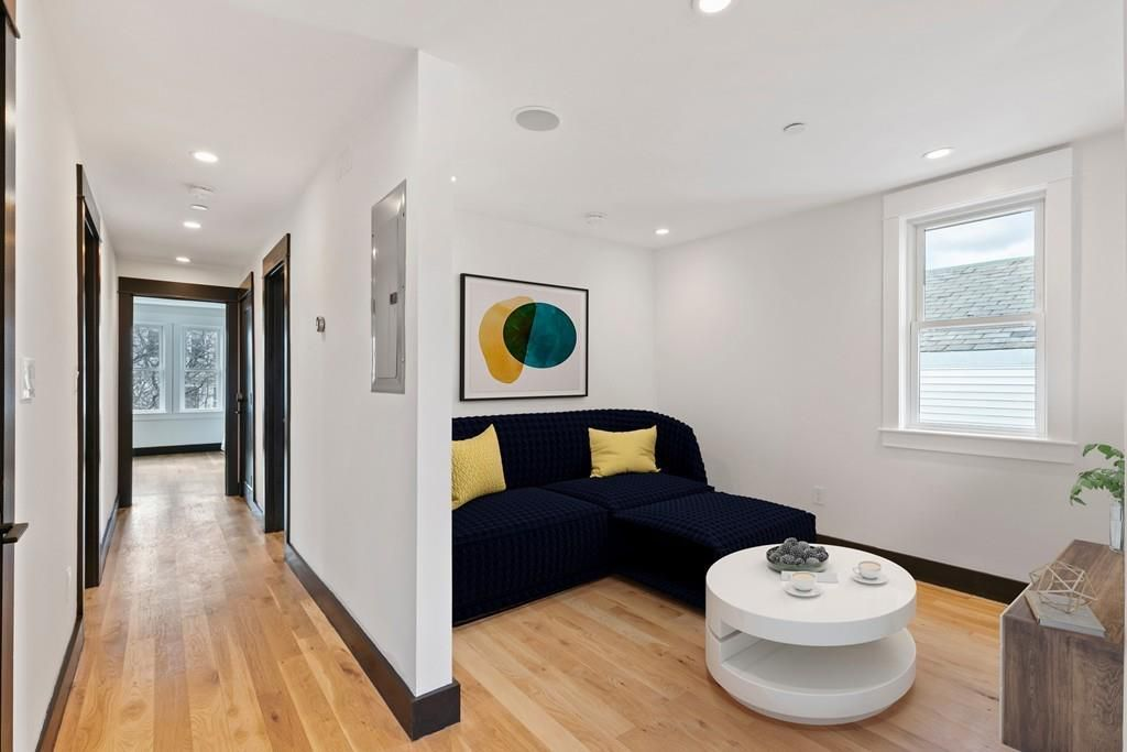 An alcove room with a couch, a window, and a small round table.