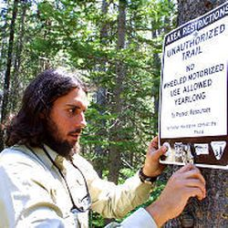 ATV ranger David DeSimone puts up a sign warning ATV users not to follow a trail that was recently widened illegally with a chain saw.