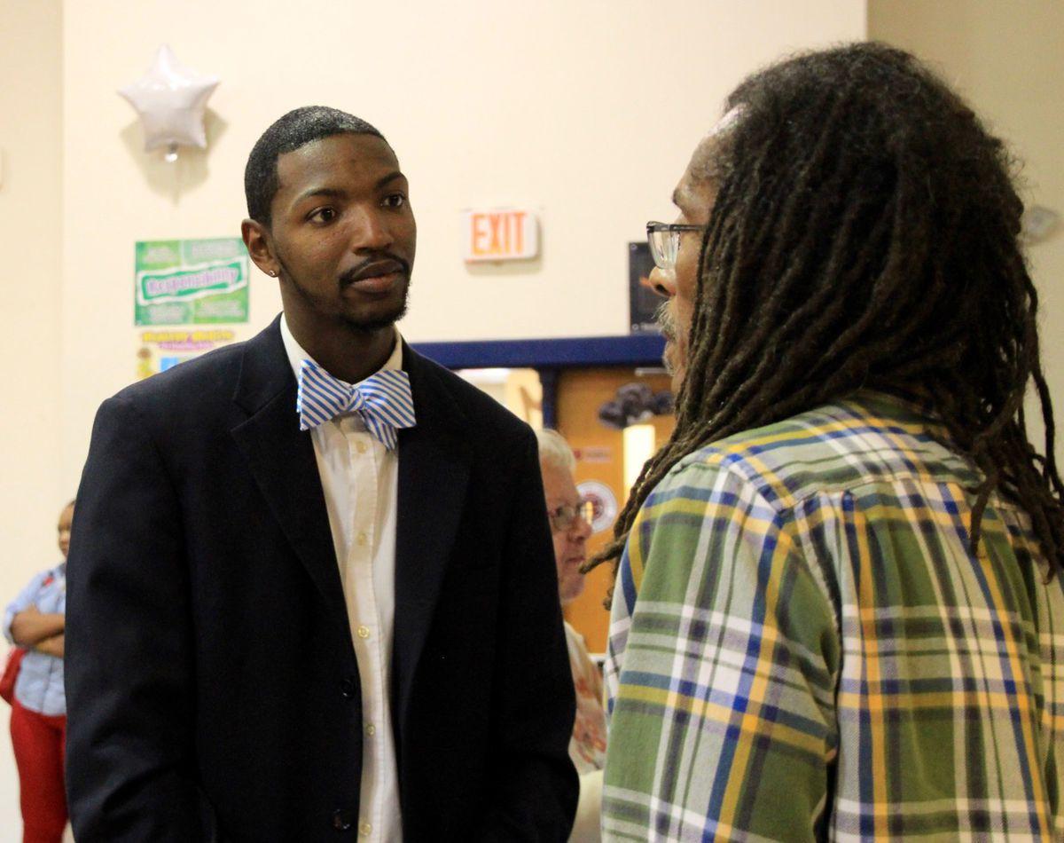 Principal Archie Moss Jr. speaks with Memphis 13 member Menelik Fombi.