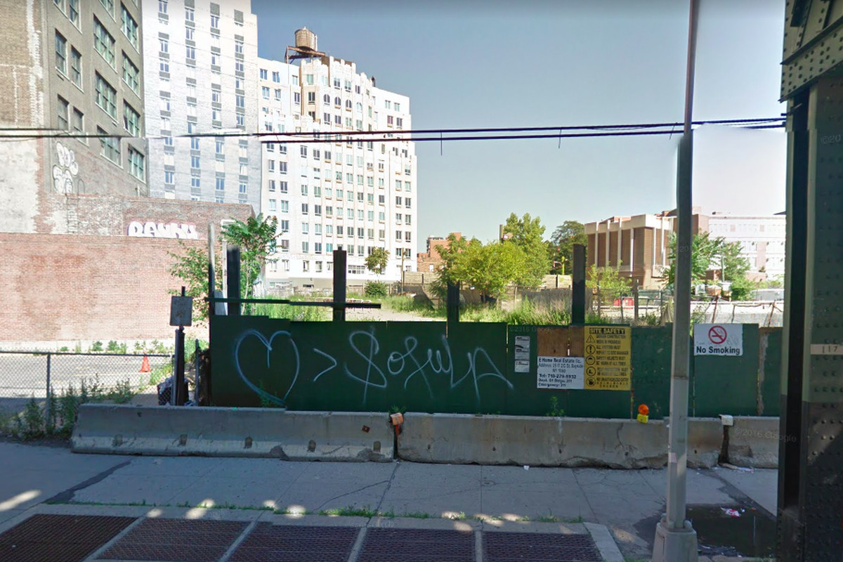 In the foreground is a sidewalk and a construction site. In the background are tall city buildings in Long Island City.
