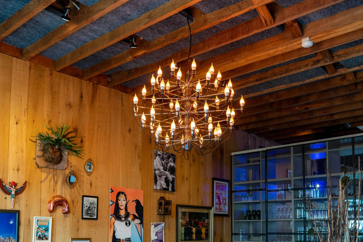 A lighted chandelier is prominently displayed in a wood-paneled private dining area at HoneyHole.