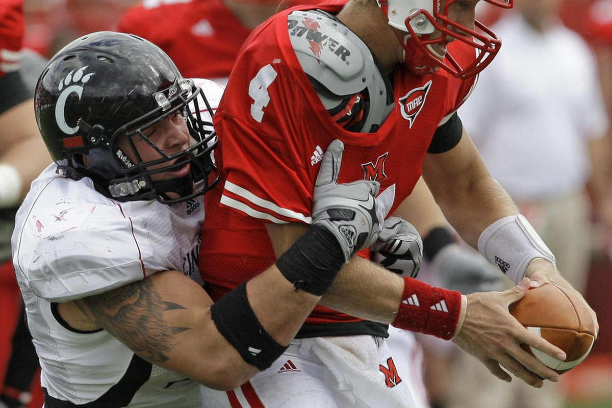 FILE - IN this Oct. 3, 2009, file photo, Miami (Ohio) quarterback Zac Dysert (4) is sacked by Cincinnati defensive tackle Derek Wolfe during the second half of an NCAA college football game in Oxford, Ohio.  Wolfe was selected by the Denver Broncos in the