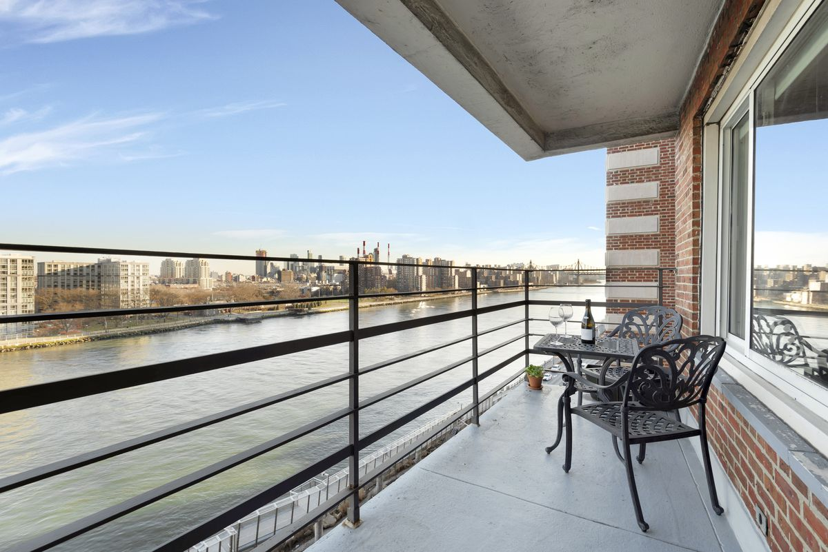 A balcony with a table, two chairs, and views of a river.