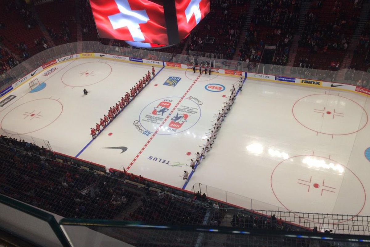 Team Canada & Team Switzerland stand at attention for anthems at an exhibition game for the 2015 World Junior Hockey Championships.