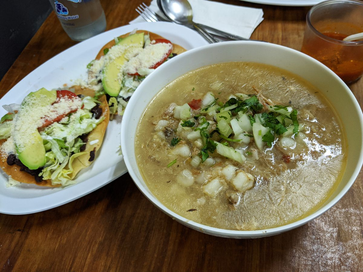 A bowl of pozole soup with nuggets of hominy and a couple of tostadas on the side.