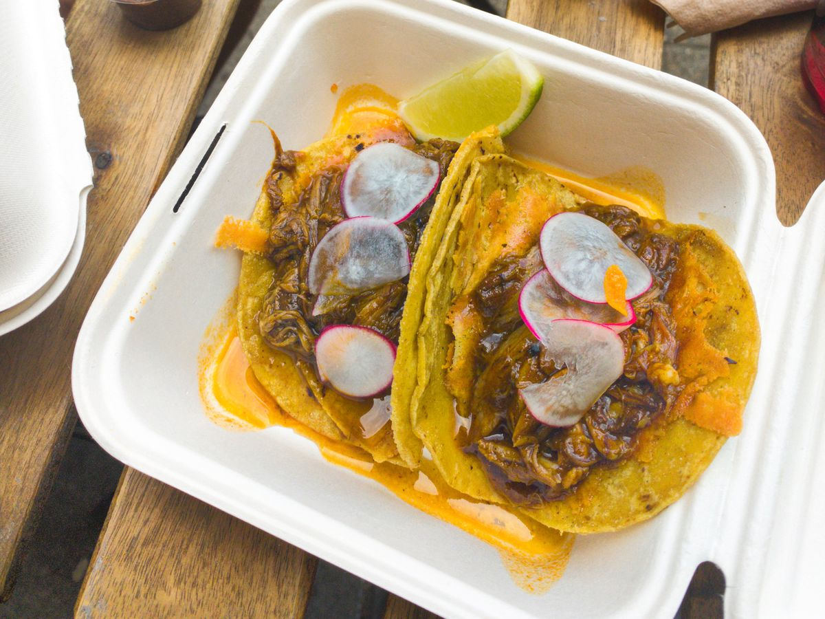 Pairs of tacos in white takeaway boxes, the corn tortillas filled with lamb birria, pickled onion, and drizzled with orange hot sauce