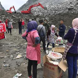 Women watch as earthmoving equipment digs at the site of a landslide in Xinmo village in Maoxian County in southwestern China's Sichuan Province, Sunday, June 25, 2017. Crews searching through the rubble left by a landslide that buried a mountain village under tons of soil and rocks in southwestern China on Saturday found bodies, but more than 100 people remained missing.
