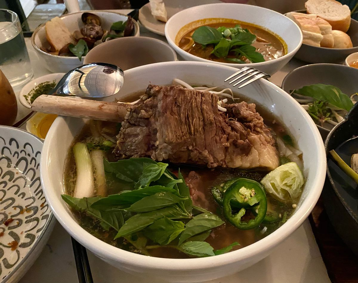 A sizable bowl of pho with scallions, basil, jalapeno, and a hunk of bone-in short rib sits on a table next to other dishes