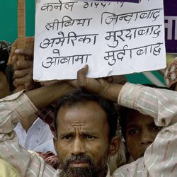 """A member of National Loktantrik Party, or National Democratic Party, holds a placard during a protest against the NATO-led Libya campaign, in New Delhi, India, Wednesday, April 13, 2011. France urged NATO on Wednesday to keep up military pressure on Libyan leader Moammar Gadhafi's forces alongside international efforts for a political solution. Banner reads """"Long Live Gadhafi and Libya. Down with America and Obama."""" (AP Photo/Manish Swarup)"""