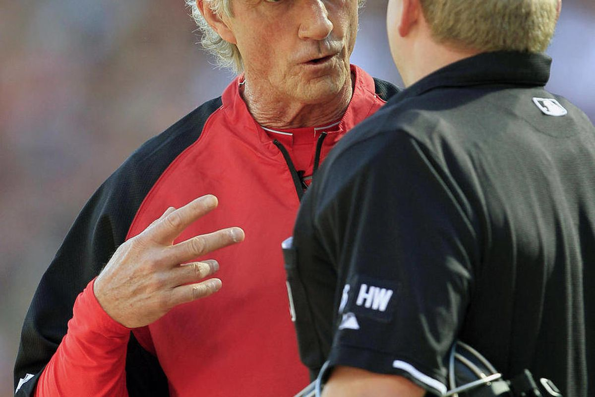 Cincinnati Reds acting manager Chris Speier, left, questions a call with home plate umpire Mike Muchlinski during a baseball game against the Los Angeles Dodgers, Saturday, Sept. 22, 2012, in Cincinnati. Reds manager Dusty Baker remained in a Chicago hosp