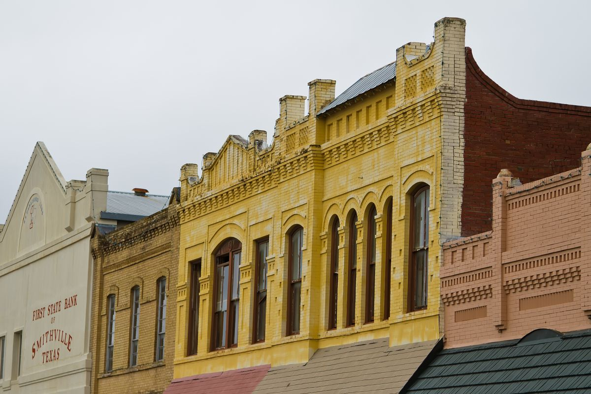 Photo of short row of second floor of old brick buildings with arched windows and columns that run from top of the first floor to slightly above the roofline.