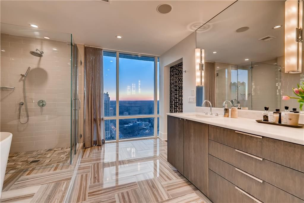 A huge master bathroom with a large glass shower and nice vanities.