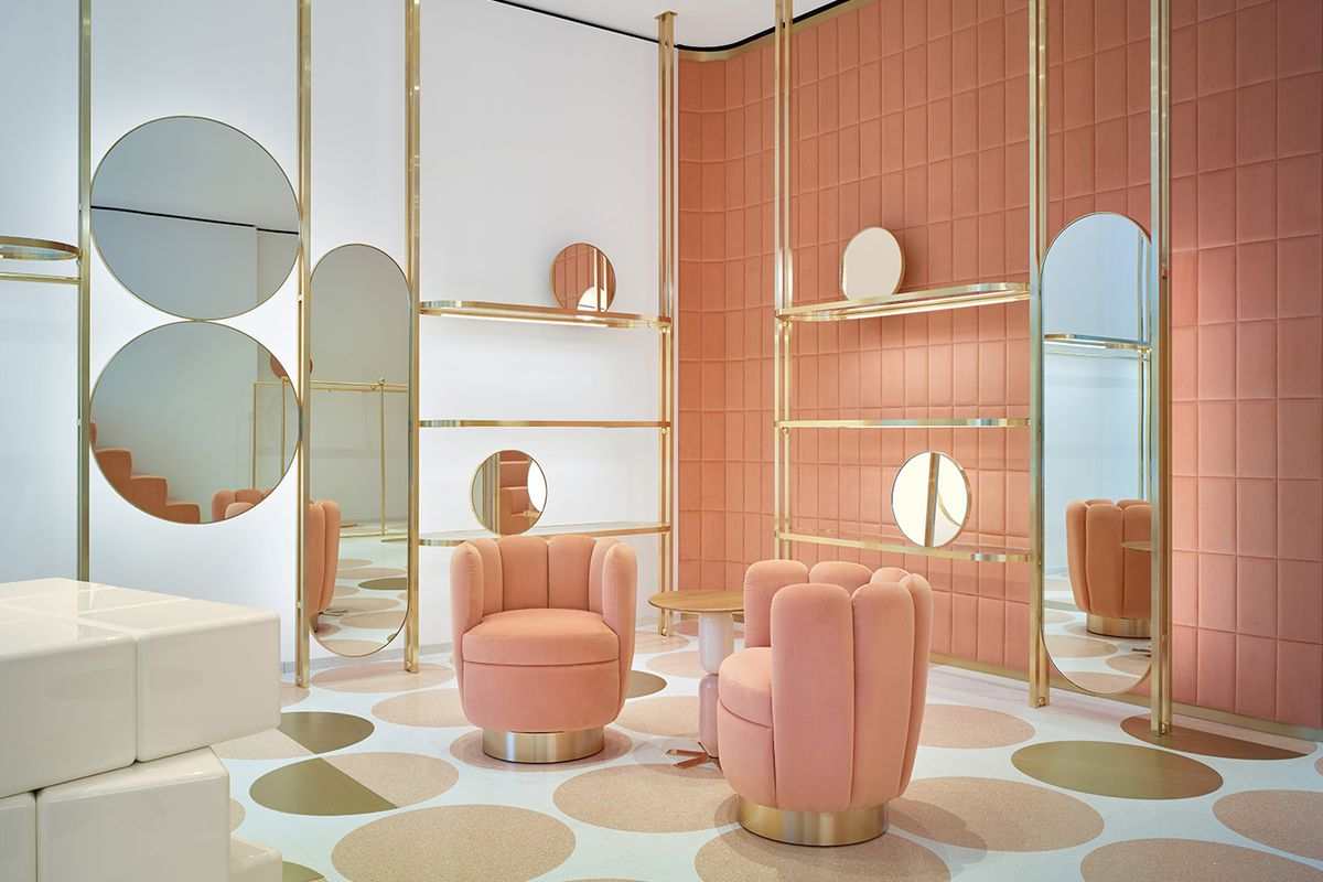 Corner of a boutique with plush pink chairs, walls, and brass trimmed circular mirrors and shelves, with a pattern of rose and gold colored circles on a white floor.