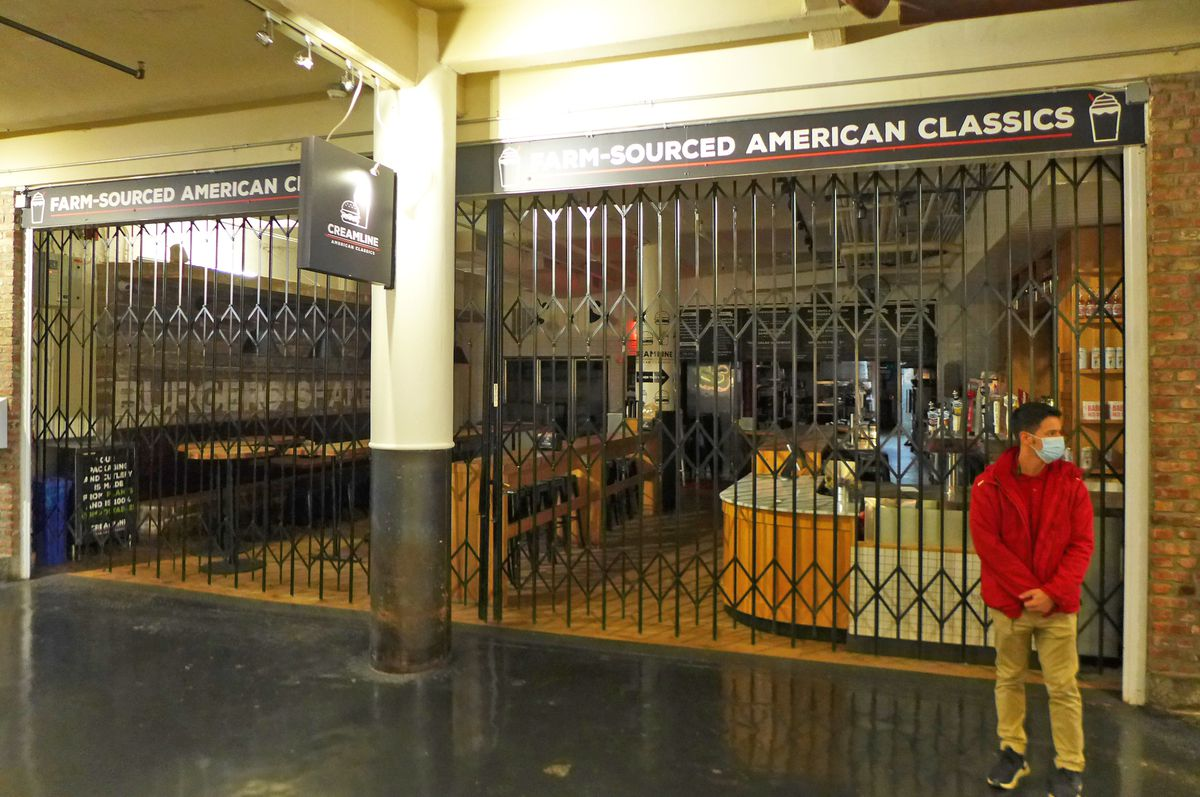 A man in a red coat stands to the right of a storefront with the security fence closed.