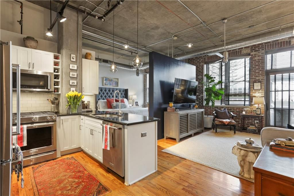 a huge loft with concrete walls and high ceilings, with a white kitchen at left.