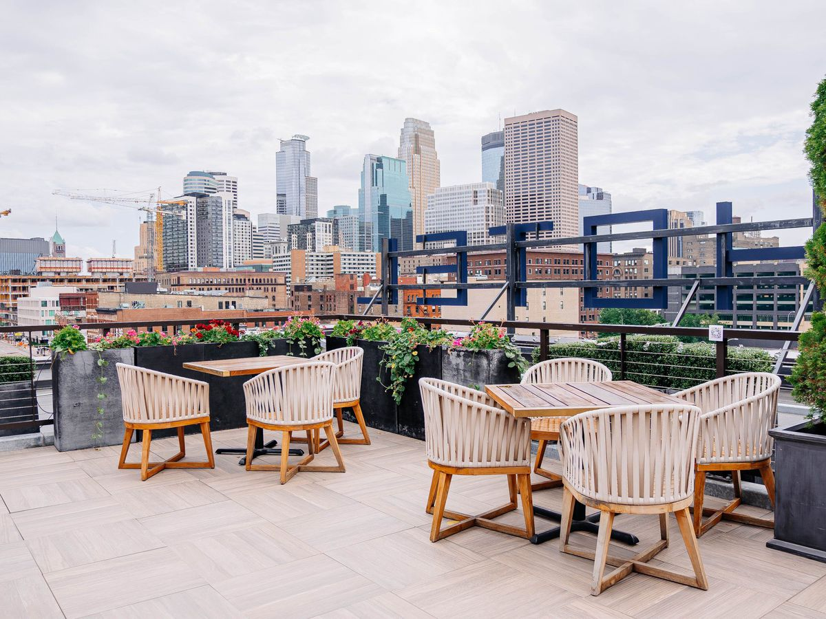 Macarame woven lounge chairs surround tables on a rooftop that overlooks the downtown Minneapolis skyline. The tables are set behind the HOTEL sign for the Hewing.
