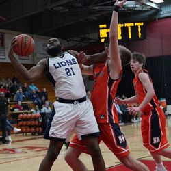 Lincoln Park's Josaphat Tamatekou (21) grabs his own rebound over Naperville North's Tom Welch (1), Saturday 02-02-19. Worsom Robinson/For the Sun-Times.