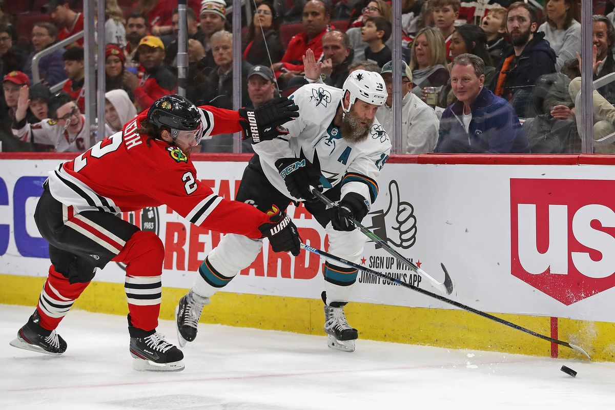CHICAGO, ILLINOIS - MARCH 11: Duncan Keith #2 of the Chicago Blackhawks pressures Joe Thornton #19 of the San Jose Sharks at the United Center on March 11, 2020 in Chicago, Illinois.