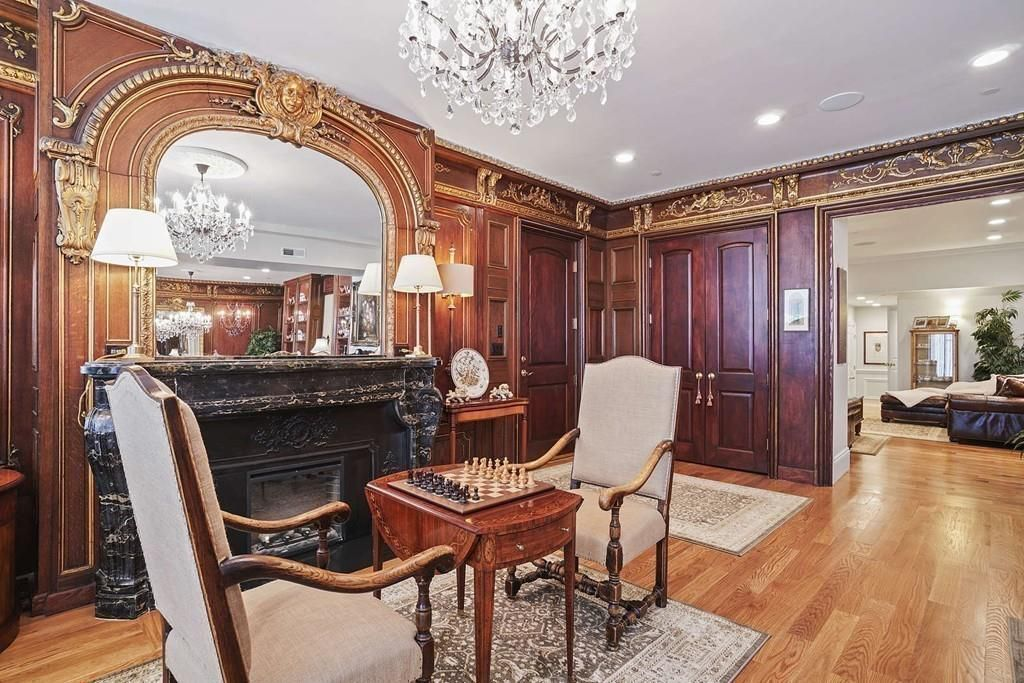 An elegant living room with a grand fireplace and a table and two chairs in front of it, and there's a chess board set up on the table.