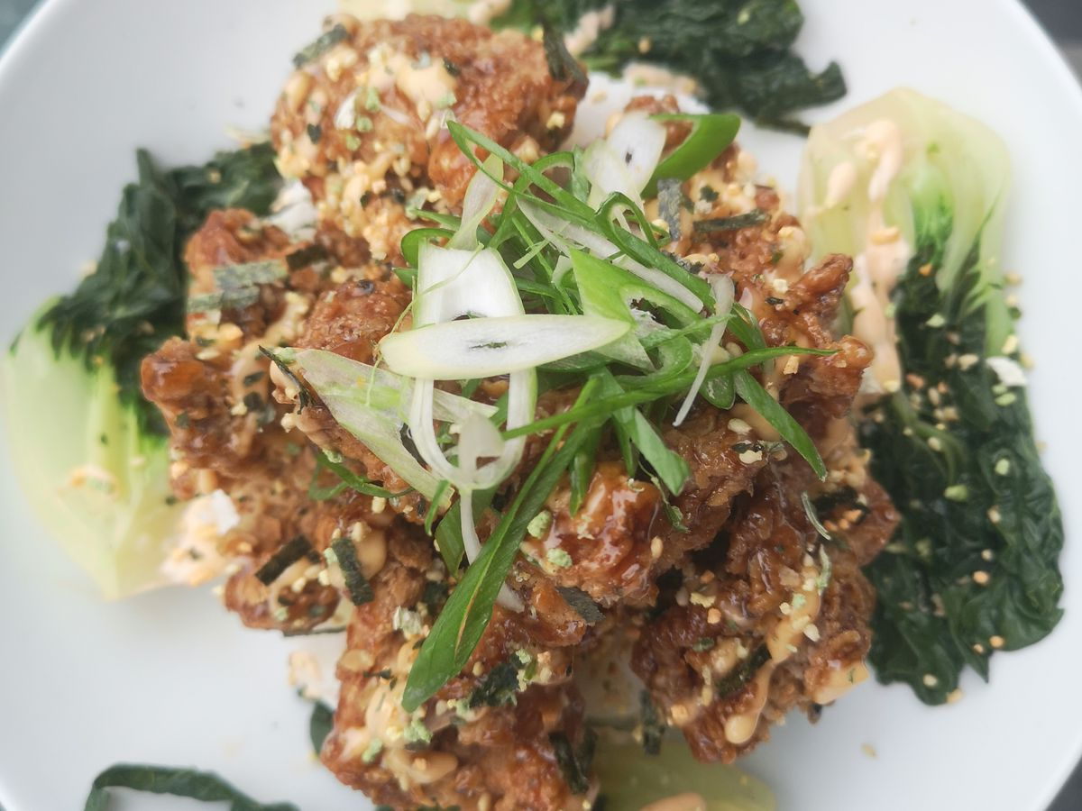 A white bowl of fried furikake chicken with bok choy beneath and green onions on top.
