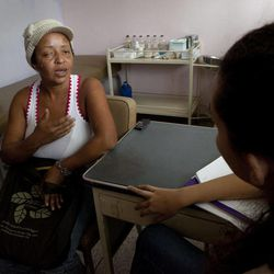 In this Oct. 28, 2013 photo, Evelina Gonzalez speaks with a psychologist at the Central Hospital in Maracay,Venezuela. She was supposed to have surgery in July following chemotherapy but was forced to shuttle from hospital to hospital in search of an available operating table, her tumor in the meanwhile more than doubling in size. The hospital's physicians sent some 300 patients in need of cancer operations home last month. Supply shortages, unsanitary conditions and equipment failures have forced them to scratch all but emergency surgeries.