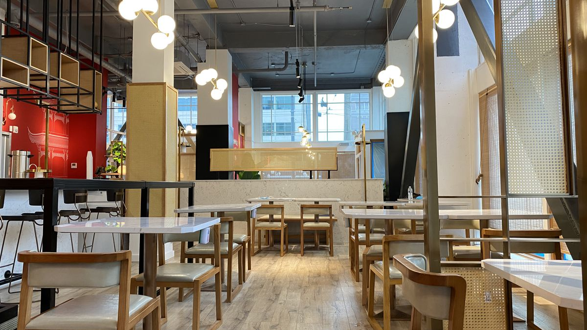 Chengdu Taste's new dining room, with tables, light wood accents, and orb-like lamps hanging from the ceiling