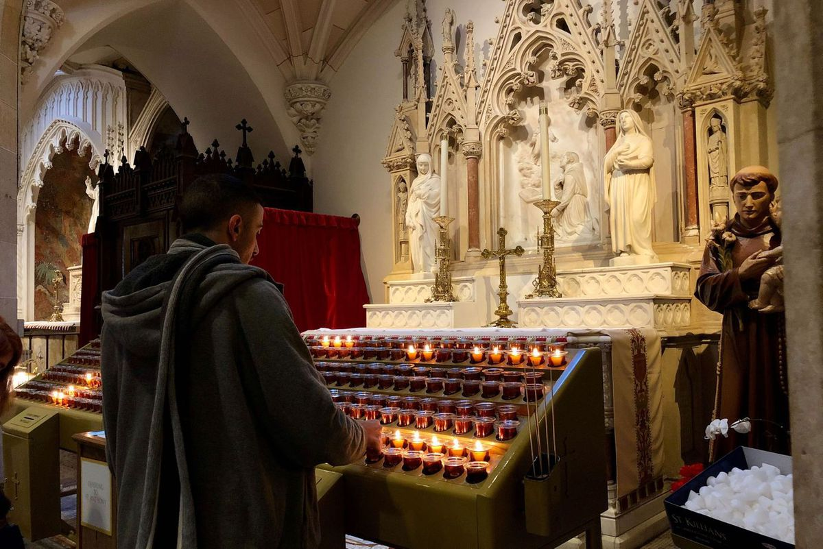 Visitors lit candles at St. Patrick's Cathedral Sunday during the coronavirus pandemic.