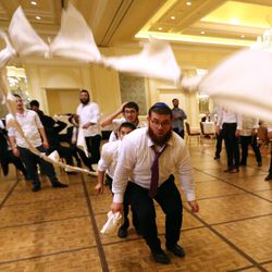 Nochum Greenwald jumps a rope made of napkins during Chaya Zippel and Rabbi Mendy Cohen's traditional Hasidic wedding at the Grand America Hotel in Salt Lake City on Monday, Sept. 12, 2016.