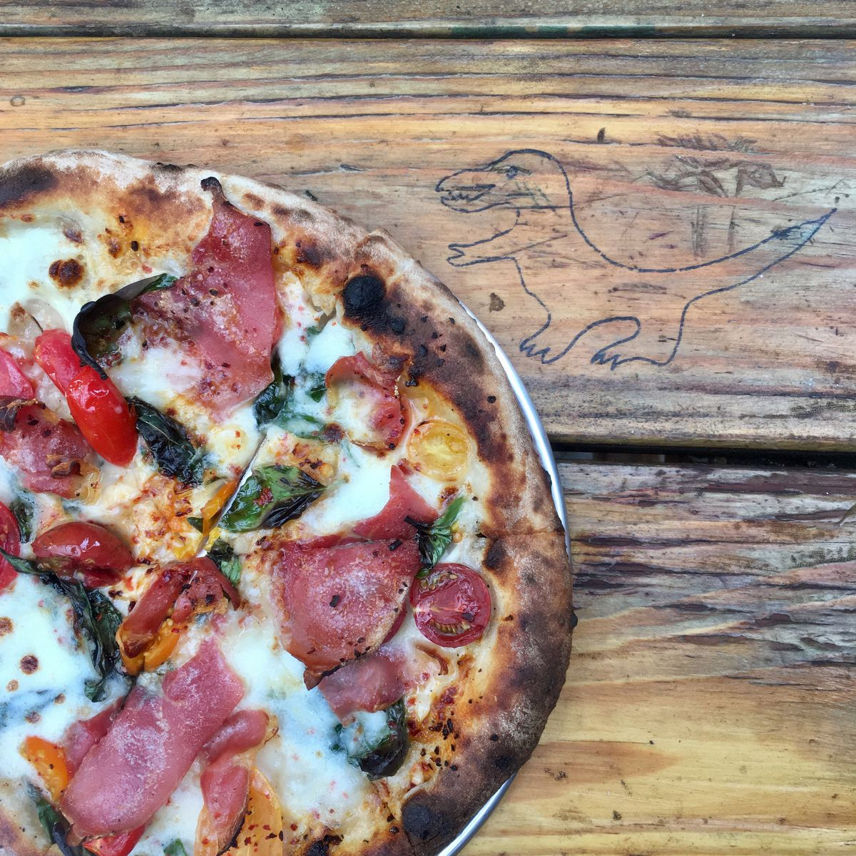 A picture of a country ham pizza with cherry tomatoes and aleppo pepper at Gracie's Apizza in St. Johns
