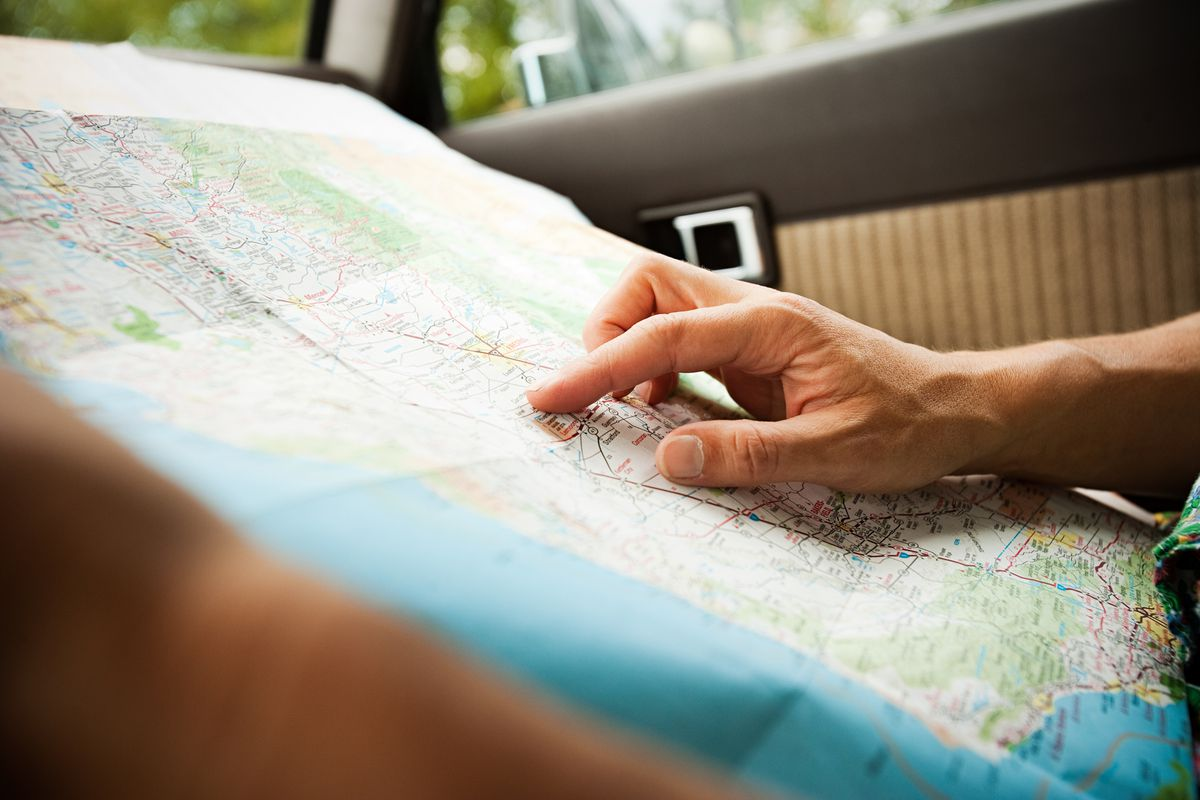 A person's hand points to a location on a map.