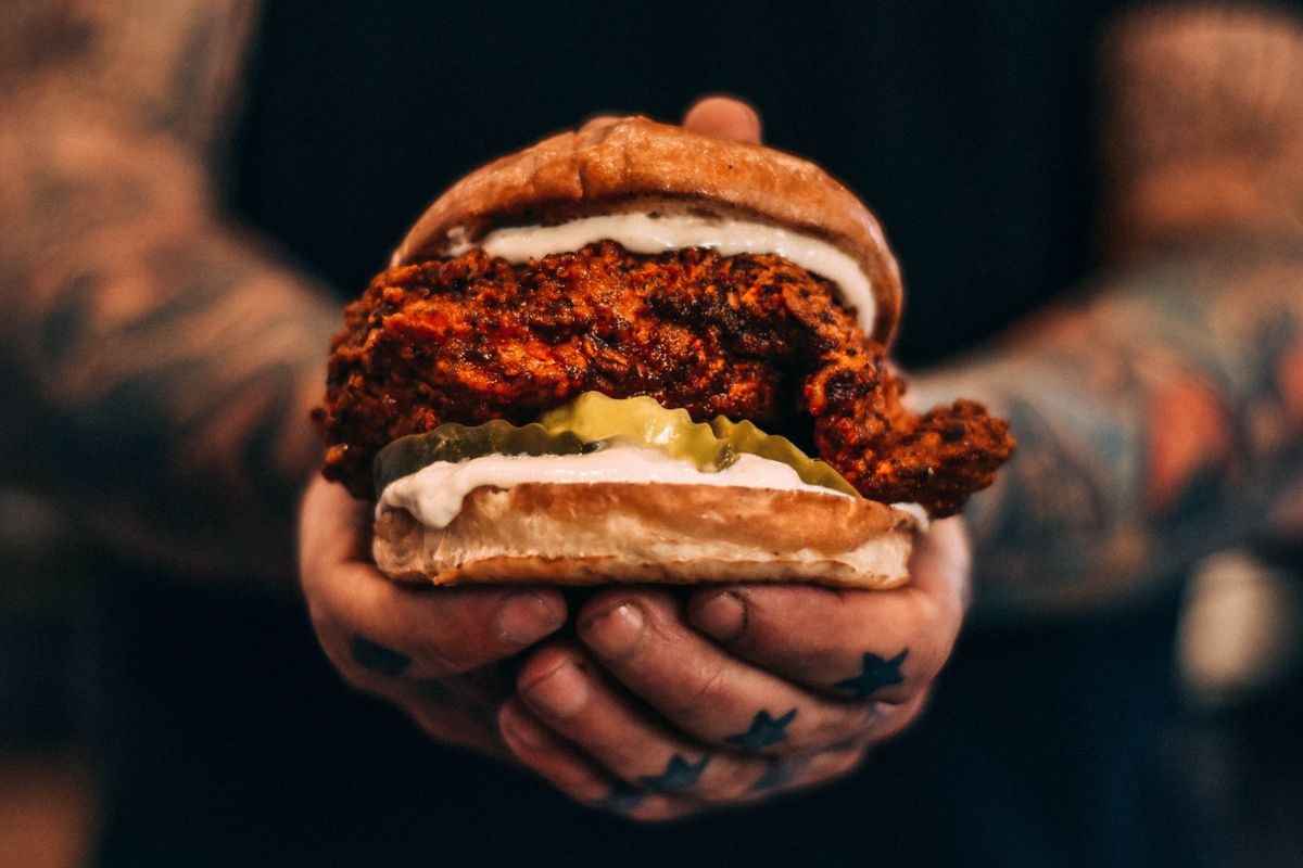 A man with tattoos holds a sandwich with fried chicken, pickles, and mayo
