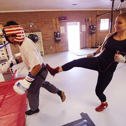 Boxer Whitney Gomez kicks at a fellow boxer who is teasing her during her workout at Fullmer Brothers Boxing Gym in South Jordan on Wednesday, June 7, 2017.