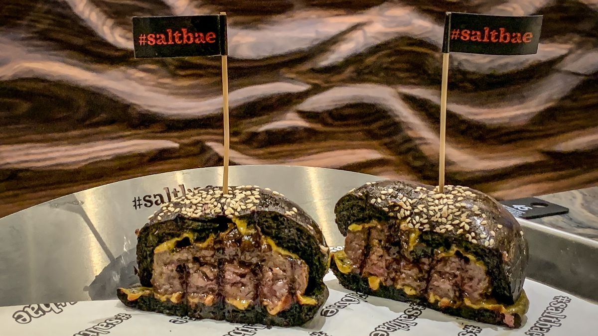 Two halves of burgers with a black bun sit on a metal tray, with toothpicks saying #SaltBae stuck in the buns.