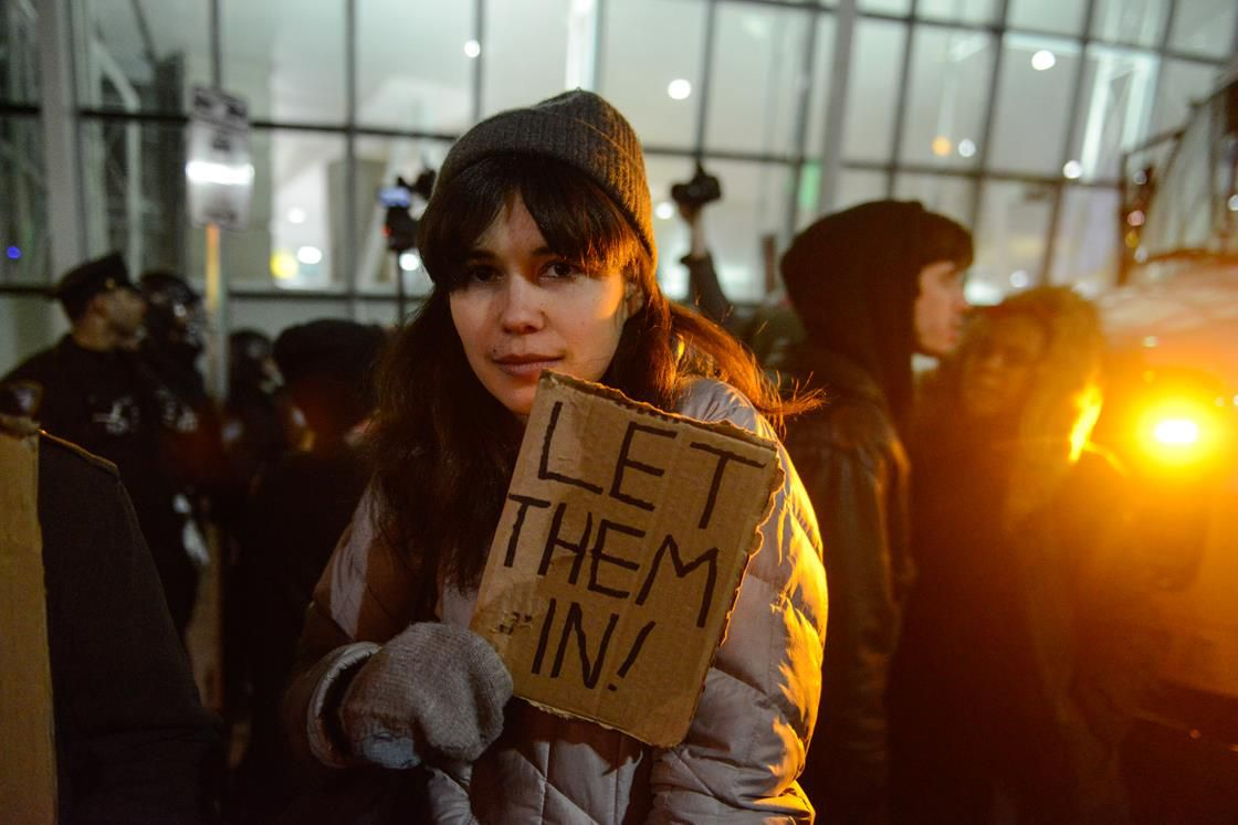 Young woman protesting Trump's immigrant order