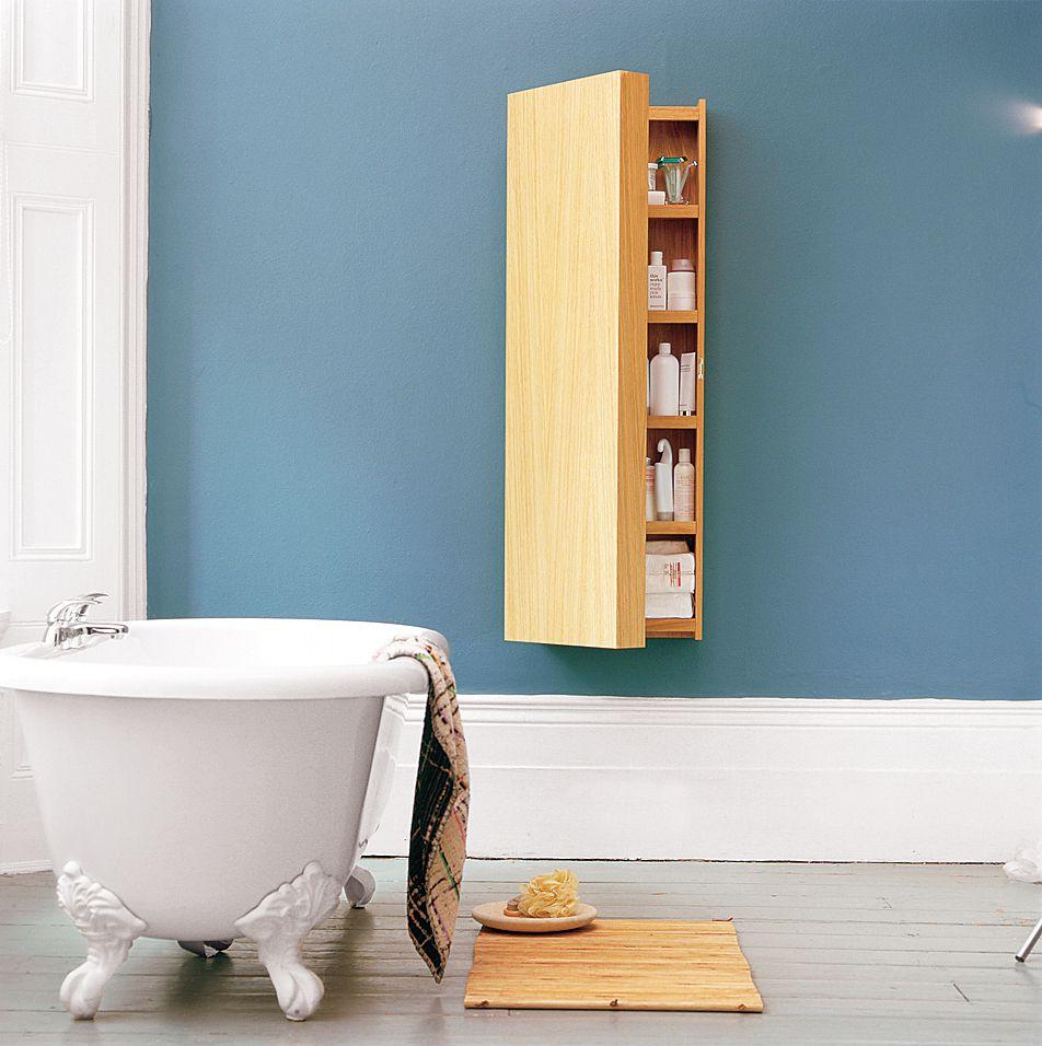 Oak wood medicine cabinet on soft blue bathroom wall.